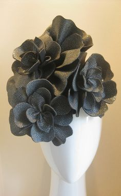 Industrial flowers. Made from the most amazing textured leather that is hard to see from the photos, but is almost like the beadwork look from the planet dress. One supersized flower and two smaller are handcut, hand stitched and balanced onto a handmade black felt base with comb and elastic for easy all day wearing. A great winter neutral - Jill and Jack Millinery