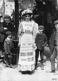 "Photograph of Suffragette demonstrating at the Strand, written on the back: ""One of the Suffragettes parading through the Strand, advertising the demonstration"". Dated 1909."