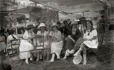 Personas sentadas, conversando bajo los toldos de la playa de la Concha el año 1919