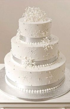 Wintery Wedding This cake is perfect for the winter bliss wedding! It is iced in buttercream with silver satin ribbon outlining the bottom of each layer. Gum paste snowflakes were added as a perfect wedding topper and great accents on each layer of cake. Publix Wedding Cake, White Wedding Cakes, Beautiful Wedding Cakes, Wedding Cake Toppers, Beautiful Cakes, Perfect Wedding, Winter Torte, Winter Cakes, Christmas Wedding Cakes
