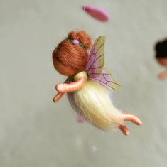 Each of the three fairies is approx. 2.7 tall and, as well as the blossoms and the falling petals, made of pure sheeps wool. The wings are made of tissue paper, which I coloured by myself. Arms and legs are movable. I have fastened them with nylon strings on a wreath of dogwood