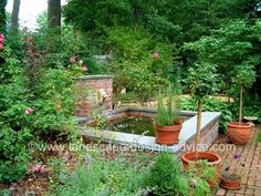 Raised water garden pond with lion's head fountain. Wall is seat height for sitting and enjoying.