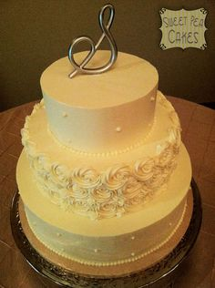Three tier buttercream wedding cake with rosettes and pearls. The picture is horrible. I only had my phone with me to snap a photo. Oh well.