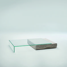 """Terraliquida, or  """"Liquid Land"""",  is a low table composed of a nature's building blocks, stone and glass. Low table composed of a parallel-piped Limestone block and a tempered 15 mm thick extra-light glass element with 45' angles that rests on top. 
