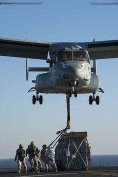 Marines attach the hoist sling of an AV-8B Harrier jet engine container to an MV-22 Osprey on the flight deck of the amphibious assault ship USS Makin Island (LHD 8)