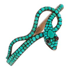 This fabulous turquoise snake bracelet is from the Victorian (ca1880) era and is simply marvelous! Made of 9kt gold and topped in silver, this ornate bracelet features pave-set turquoise stones and small garnet eyes.