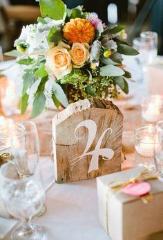 Números para mesas de boda pintados a mano sobre bloques de madera.
