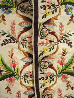 """Detail of exquisite embroidery and matching covered buttons to the front of an ivory silk faille waistcoat, part of a """"Habit a la Francaise""""  consisting of Frock Coat and waistcoat, France, 1770-1790."""