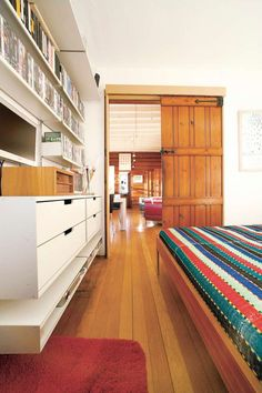 Whether older house or newer, your shelves are equally at home. Here the DVDs allow bed-time cinema while the clothes hide in the drawers. OrderlyPhotography Philip Lauterbach