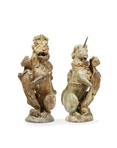 A rare pair of James I polychrome-decorated and parcel-gilt carved oak heraldic newel finials, the Lion and Unicorn supporters of the Royal Arms (2)