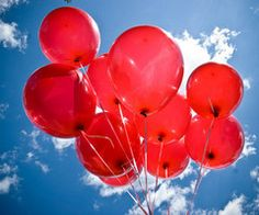 Up, up, and away! Red balloons set against a brilliant blue and white sky