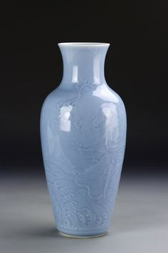 China, 18th C., celadon vase, rounded shoulders, tapered neck, sky blue glaze incised with dragon motif, Qianlong mark on base. Height 13 in.