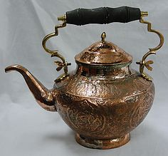 Antique Persian Copper Teapot. decorated with embossed and engraved scrolls and flower motifs along with several figural birds. Attached handle with wooden hand-hold.