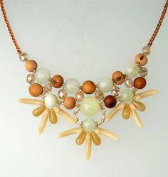 Tuca Stangarlin. XAF004. Colar folheado a ouro, terminado em trança de fio de seda com chuva de cristais; medindo aproximadamente 60 cm. Material: Semente de açaí, jade, murano e Cristal Tcheco.