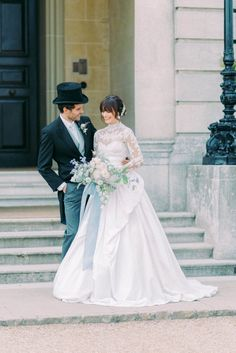 hedsor house spring summer wedding inspiration; bride wearing a white long sleeves chantilly lace marchesa wedding gown with full ball gown skirt; seasonal bridal bouquet; groom wearing a black top hat, long coat and pale blue vest and neck tie; in front of hedsor house entrance   Photo by London and Newcastle UK based light bright and airy Filipina wedding photographer Cristina Ilao