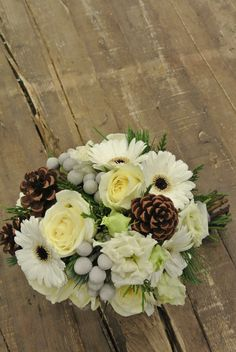 White bridal bouquet with gerberas, roses, lisianthus, brunia, pine cones, pines and cedars. Designed by Forget-Me-Not Flowers in Banff.