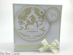 """A further card in my 2014 Handmade Christmas Card range and uses a beautiful pale gold and white colour scheme.  The card is 5.5"""" x 5.5"""" square and hinges at the top of the card. It is built with multiple layers, with a pretty white spotty embossed panel as the main background.  Mounted on this handmade Christmas card is a beautiful die-cut Tattered Lace snowglobe motif featuring a Christmas tree, church, moon and snowflakes."""
