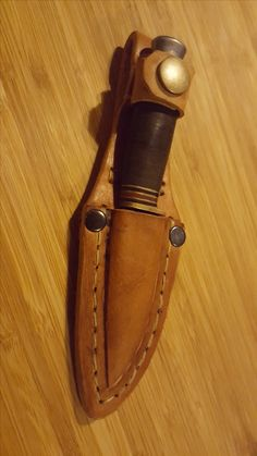 Veg-tanned leather knife case for small fishing knife.