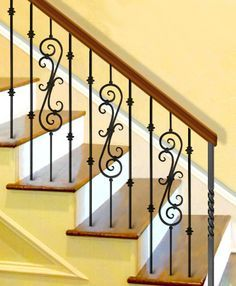 Staircase design pattern with long decorative iron scroll and double bushing balusters. Staircase Railing Design, Interior Stair Railing, Wrought Iron Stair Railing, Home Stairs Design, Wrought Iron Decor, Stair Handrail, Modern Staircase, Stair Design, Railing Ideas