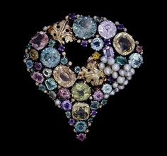 Dorrie Nossiter. An Arts and Crafts silver and gold brooch set with blue zircons, pink tourmalines, pale emeralds, green beryl, yellow and white sapphires, amethysts, pearls, one tiny yellow paste stone and accentuated with golden beading and leaves, c. 1930. Size: Approx. Height 5.5 cm. Width 5.2 cm. Fitted case. Sold by Van Den Bosch.  View 2.