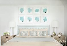 Shades of blue and sandy taupe keep the mood cool and calm in the ocean suite. The custom linen headboard is accented by throw pillows from Bungalow Classic and bedding from Gramercy Home. The bedside tables are from Bungalow Classic. Lamps are from Visual Comfort, and artwork is from Wendover Art Group.