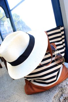Perfect summer accessories: a Panama hat, aviators and a striped tote bag.