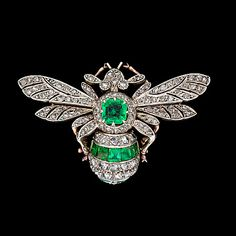 An emerald and diamond brooch, c. 1900. Gold/silver.