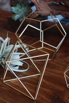 """Geometric gold prisms for decor and centerpieces. Small: Octahedron: 2"""" l x 2"""" w x 5"""" h Qty: 2 Dodecahedron: 3.5"""" l x 3.5"""" w x 4"""" h Qty: 1 Diamond: 2.75"""" l x 2.75"""" w x 4.5"""" h Qty: 2 Star: 3.5"""" l x 3.5"""" w x 4.5"""" h Qty: 2 Large: Octahedron: 12"""" l x 6"""" w x 6"""" h Qty: 12 Dodecahedron: 9"""" l x 9"""" w x 9"""" h Qty: 2 Diamond: 10.5"""" l x 5.5"""" w x 5.5"""" h Qty: 11"""