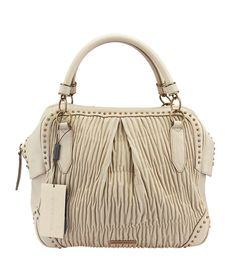 Burberry Beige Plissé Leather Studded Tote--$805 #BurberryHandbags #BurberryTotes Buy this bag on our site, now! http://www.cashinmybag.com/product/burberry-beige-plisse-leather-studded-tote/ This Burberry Plisse leather tote is brand new with tags, showing no signs of previous wear. It features a zippered top closure, two rolled leather handles, and studding around the bottom and top of the bag.