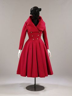 """Hardy Amies designed this cotton day dress at the end of the Second World War. The dress has magyar sleeves (in which the armhole and upper arm are cut very wide, narrowing to the elbow and wrist), a tightly fitted bodice and a dropped waist. The circular skirt is embellished with a fashionable bustle bow."