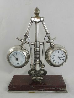 A silver plated French industrial series ''Centrifugal Governor'' clock (not automated), bevelled gear to base, articulated arms appear as part of a governor, the balls containing clock to one side, barometer to the other, both with white enamelled dials, red marble base with silver plated metal border, 31cm high, Circa 1885