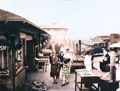 Fisherman's Wharf, 1920 -- During the early 20th century, Italian immigrants were the primary fishermen on the San Francisco Bay. They sold their catches from small stands on Fisherman's Wharf and set up cauldrons of boiling water to cook freshly caught crabs, dispensed to visitors in paper cups. (via Business Image Group | Handtinting by Bennett Hall)