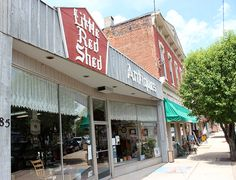 """Located in Waynesville, Little Red Shed Antiques offers a wide range of antique nick-nacks, art, and furniture. You can find """"Howard Products"""" which are used for restoring and maintaining finishes on all wood items."""