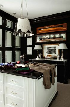 source: Luis Bustamante  Walk-in closet with floor to ceiling glossy black & white cabinets, white closet island with wood top, black buffet with marble top and polished nickel pendant.