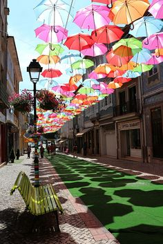 This beautiful installation of umbrellas was recently spotted in Águeda, Portugal by photographer Patrícia Almeida. Almost nothing is known about the artist behind the project or its significance, but it's impossible to deny the joy caused by taking a stroll in the shadowy rainbow created by hundreds of parasols suspended over this public walkway