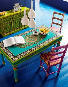 Okay, I don't really like THIS table, but I like the idea of having a colorful dinner table???? paint a door and lay plexiglass over the top. Then collect different random chairs to go with the table. Eveyone picks their own??? Oh my gosh........my wheels are turning!
