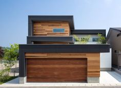 Modern wooden facade with wooden garage door and small natural touches. By Architect Show co.,Ltd