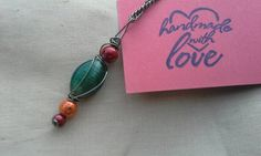 Check out this item in my Etsy shop https://www.etsy.com/listing/242443362/wire-wrapped-teal-orange-and-red-pendant