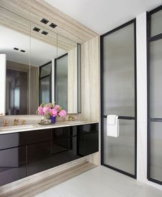 The master bath hits every note with a silver travertine vanity surround and custom-fitted shower doors | archdigest.com
