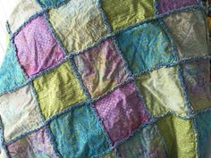 Full size rag quilt in batiks and denim with soft turquoise, lime, lavender, and ivory colors and washed blue denim back