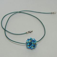 The yummy little bead on this necklace is created by weaving together tiny Swarovski crystals. At 16 inches in length, it sits perfectly around your neck. The bead is just over 1/2 inch wide strung onto a teal colored leather cord that secures with a sterling silver hook and eye clasp. A beautifully simple but sparkling addition to your jewelry box.  $25.00