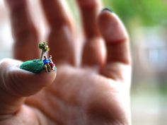 Alice Bartlett cut some pieces of green flocking to fit over her fingernails where she staged and photographed a series of scenes using miniature figurines to turn each green nail into its own little island.