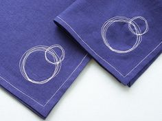 """This particular set of 4 napkins is navy blue with white contrasting stitching. The corners are all beautifully mitered and each are embellished with a circle stitch as shown. They measure 10"""" square. $10"""
