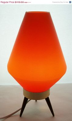"Rare Vintage Eames Era Mid Century Modern Atomic Orange Lamp Danish Modern Teak Legged Tri-Pod Base Table Lamp. Plastic Ribbed Orange Shade 1950s. This lamp is in excellent working condition, some small tarnish spots on the metal base.  Stands 14"" tall with the shade, about 9"" wide at the widest part  Teak wood legs are 3"" tall  shade 12"" tall"