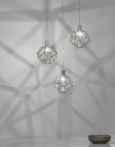 A CELESTIAL SUSPENSION OF INTERWOVEN NICKEL-PLATED METAL SHAFTS, ETOILE TWINKLES IN ALL DIRECTIONS CREATING A GENTLE PLAY OF LIGHT AND SHADOW FOR ANY SPACE. DESIGN CHRISTIAN LAVA.
