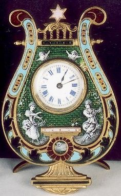 A MINIATURE FRENCH TIME PIECE. Lyre-shaped with green enamel inset field enameled with white figures of man and woman with cherubs above, the border in turquoise and red enamels, star of David at crest. The clock dial in white with blue Roman numerals having gold star dividers. Key built-in back and stand. Height 3 in., width 2 in. Late 19th century.