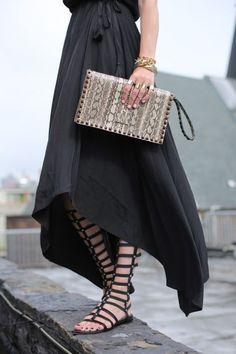 アシンメトリーなスカートの裾からのぞくグラディエーターサンダルから、女性の強さを感じさせる着こなし。
