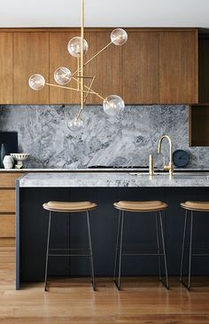 Kitchen - Wood cabinets with black island and gray marble countertop kitchen details