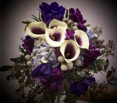 So gorgeous! bouquet includes purple and ivory calla lilies, 3 other purple shade flowers and sage-colored greenery plus some small white flowers (not baby's breath)