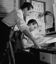 Ward Kimball drawing Jiminy Cricket while Walt Disney looks on, November 8, 1939.